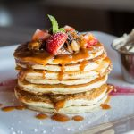 Stack of pancakes with strawberries and syrup
