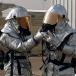2 people dressed in hazmat suits
