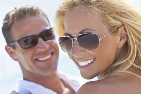 Closeup of adult couple wearing sunglasses, smiling