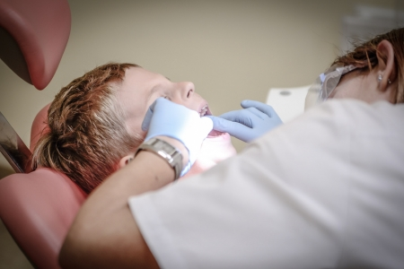 Young boy having teeth inspected by dentist